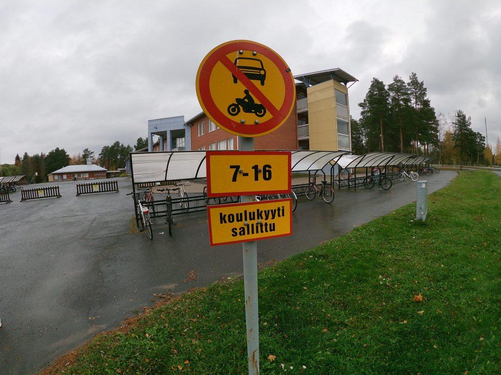 Koulutaksit ajavat suoraan koulun pihalle, pyöräparkkien välittömään läheisyyteen. Fiksusti kouluun -asiantuntijat ehdottivat koulutaksien noutopistettä ajotien reunaan koulun pihan sijasta.