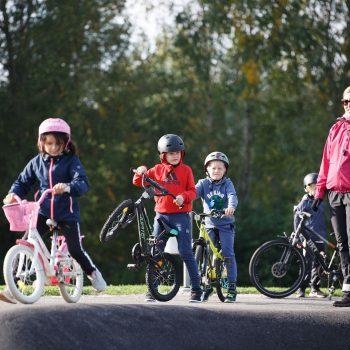 kolme pyöräilevää oppilasta pumptrack-radalla. Opettaja seuraa sivussa.